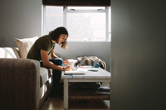 Student writing notes sitting on a couch beside a window at home. Young man studying with laptop and books on table.