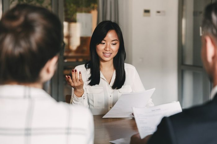 Business, career and placement concept - businesslike asian woman holding resume and speaking to employers of big company during corporate meeting or job interview