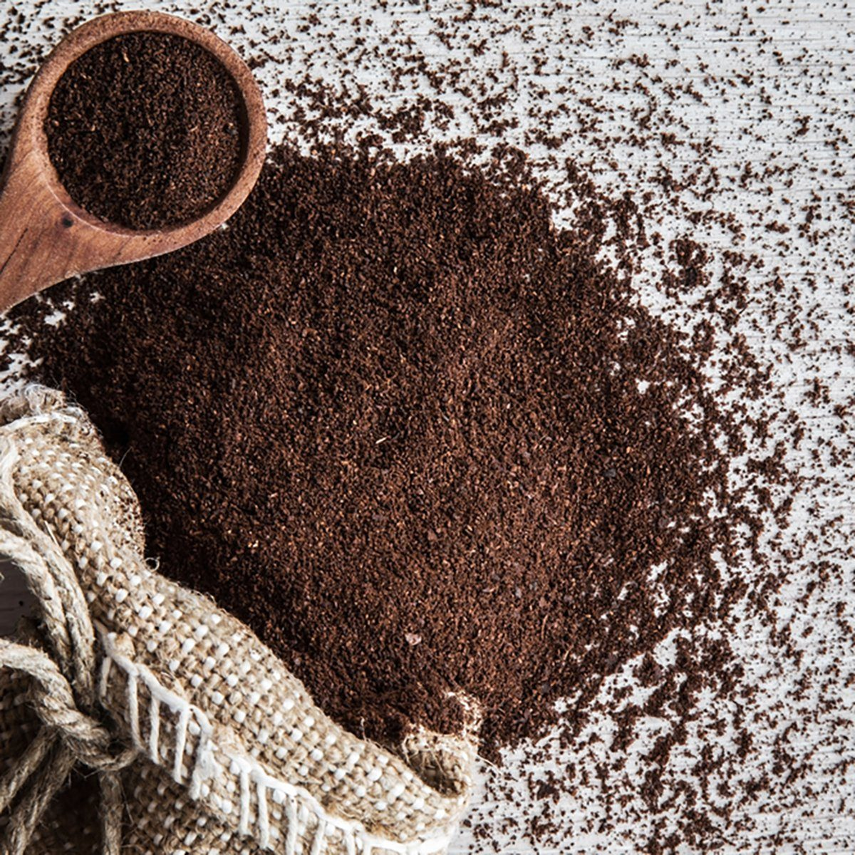 Ground coffee with burlap bag on the wooden table in the kitchen