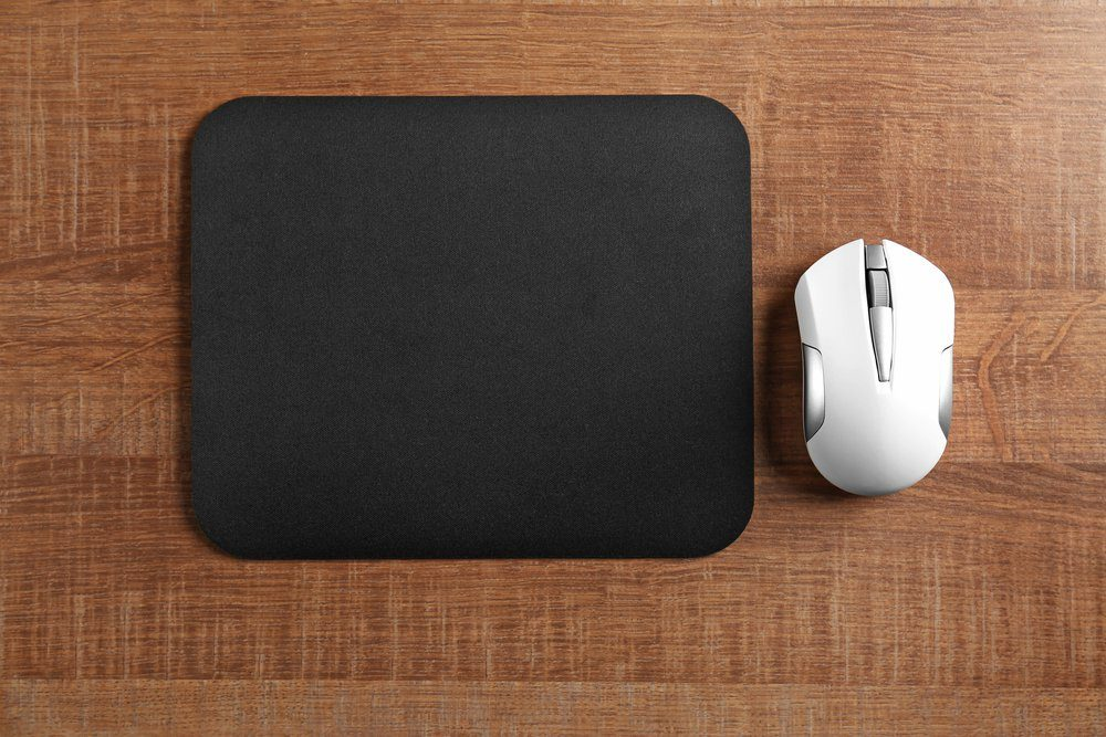 Blank mat and wireless mouse on wooden background
