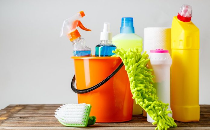 Bucket with cleaning items on light background