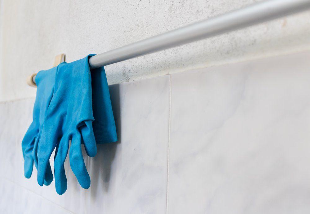 Blue glove hanging on towel rack in bathroom.
