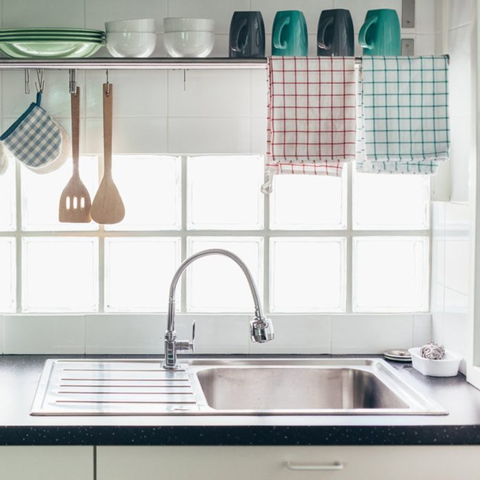 Home kitchen interior. Cooking utensils on a railing system and shelf with dishes above a window.; Shutterstock ID 698380921