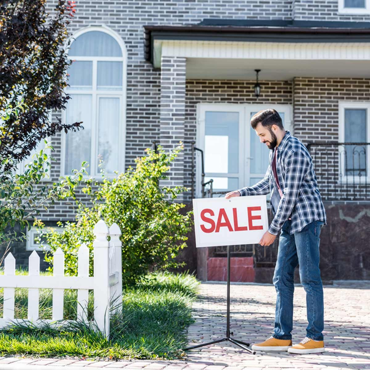 young man with sale board selling his house