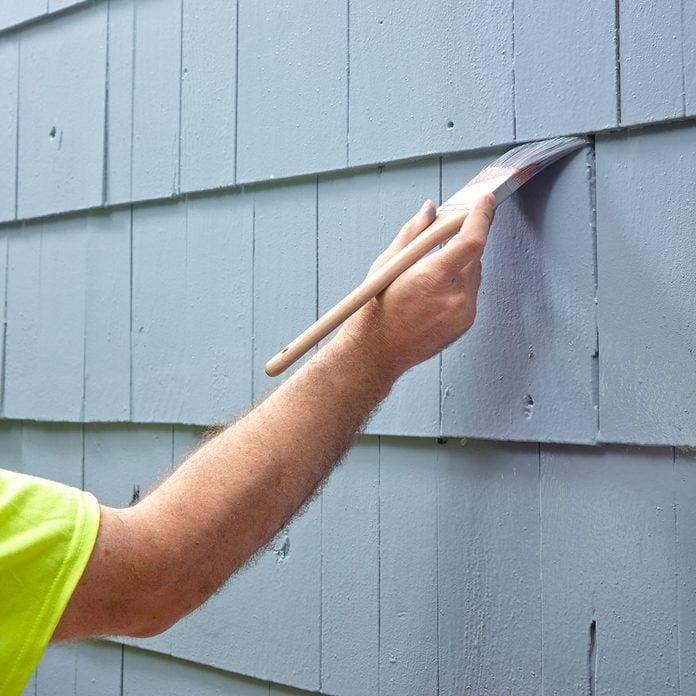 brushing paint on to siding   Construction Pro Tips
