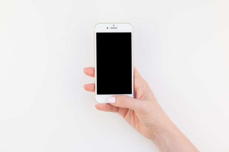 BERLIN, GERMANY - JUNE 22, 2018: Woman hand with pastel manicure polish holding Iphone 7 isolated on white background with copy space in minimalism style