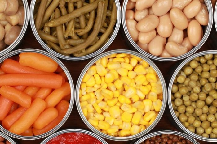 Different kinds of vegetables such as corn, peas and tomatoes in cans