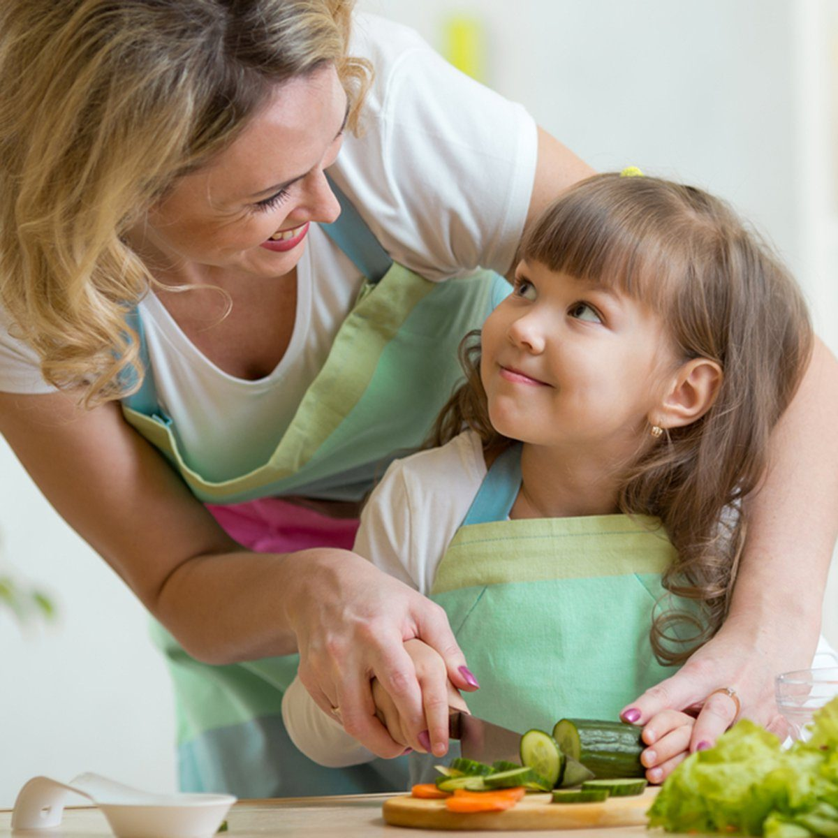 mother and kid girl cooking and cutting vegetables on kitchen; Shutterstock ID 253719916