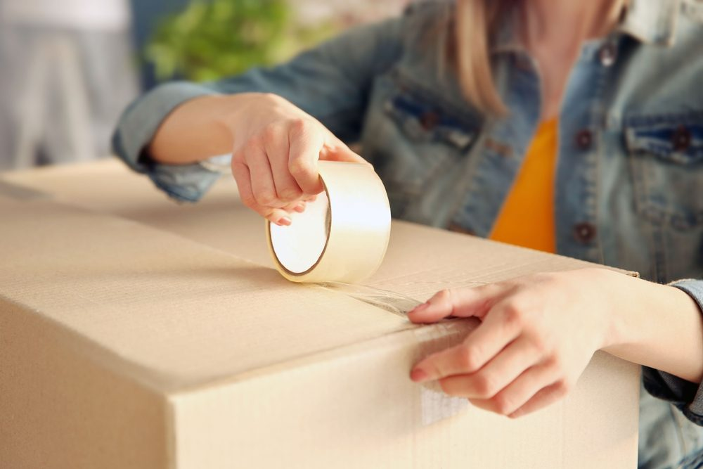 Young girl sealing with tape big cardboard box for moving