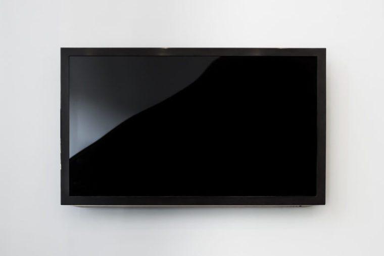 Black LED tv television screen mockup / mock up, blank on white wall background