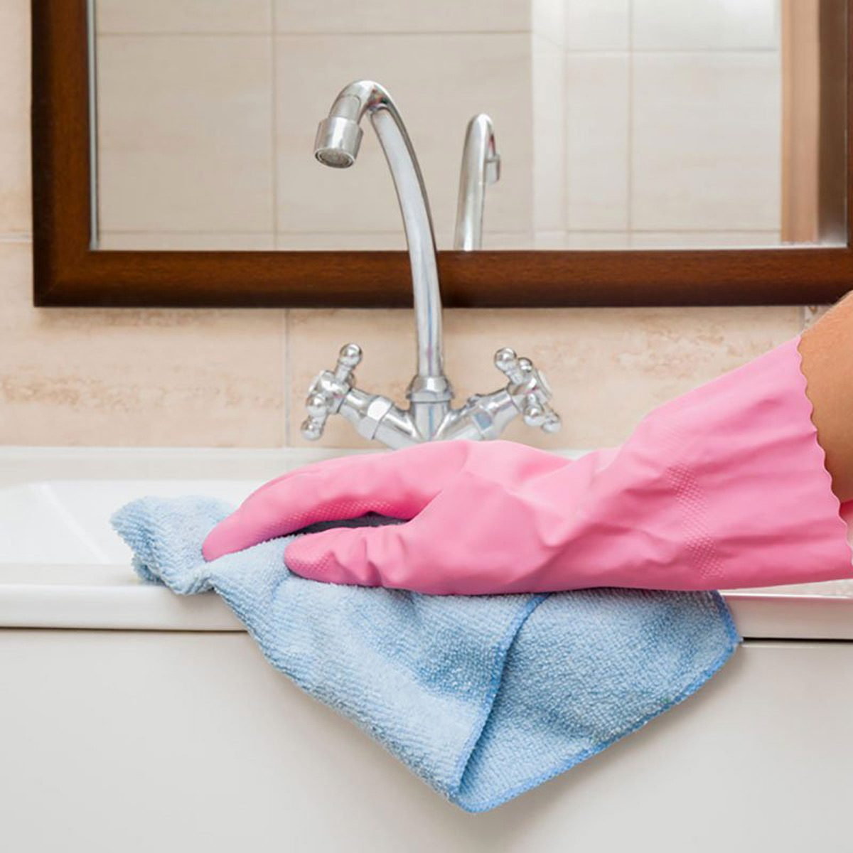 In the bathroom, hand in rubber protective glove cleaning with microfiber cloth washing and polishing ceramic sink and water tap