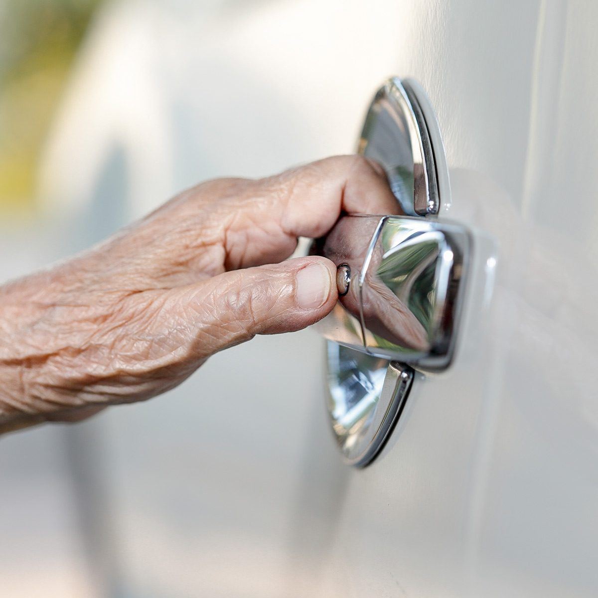 elderly woman hand opening car door