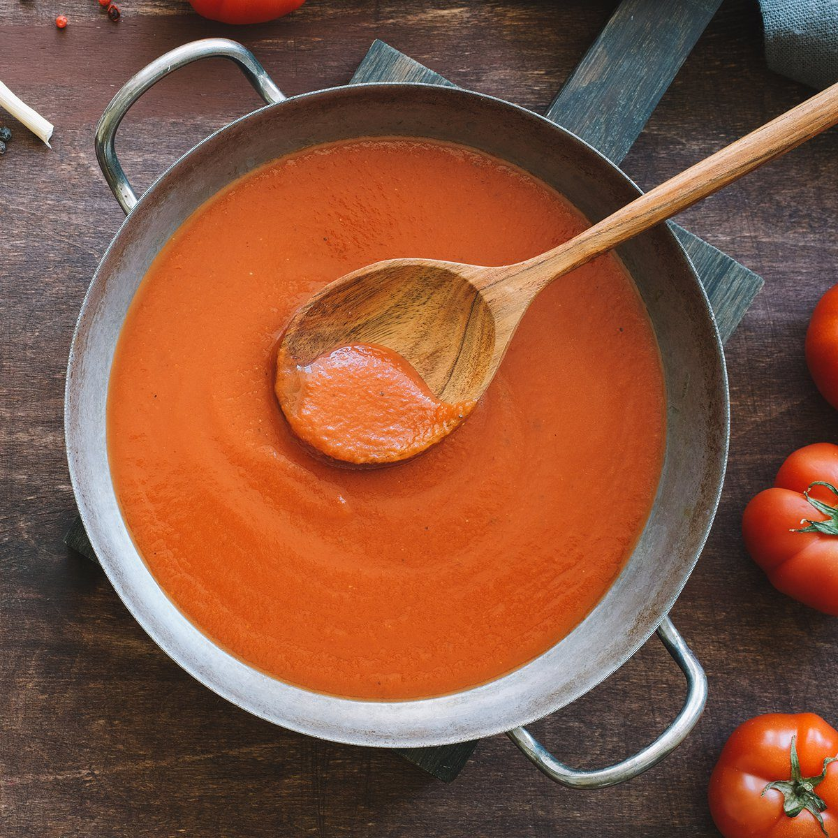 Tomato sauce in pan. Top view wooden brown background; Shutterstock ID 1380828656; Job (TFH, TOH, RD, BNB, CWM, CM): TOH