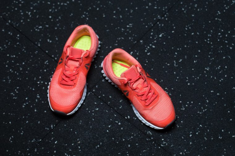 Top view of bright crimson sneakers for women, shoes for sports routine on a dark blurred background, copy space.