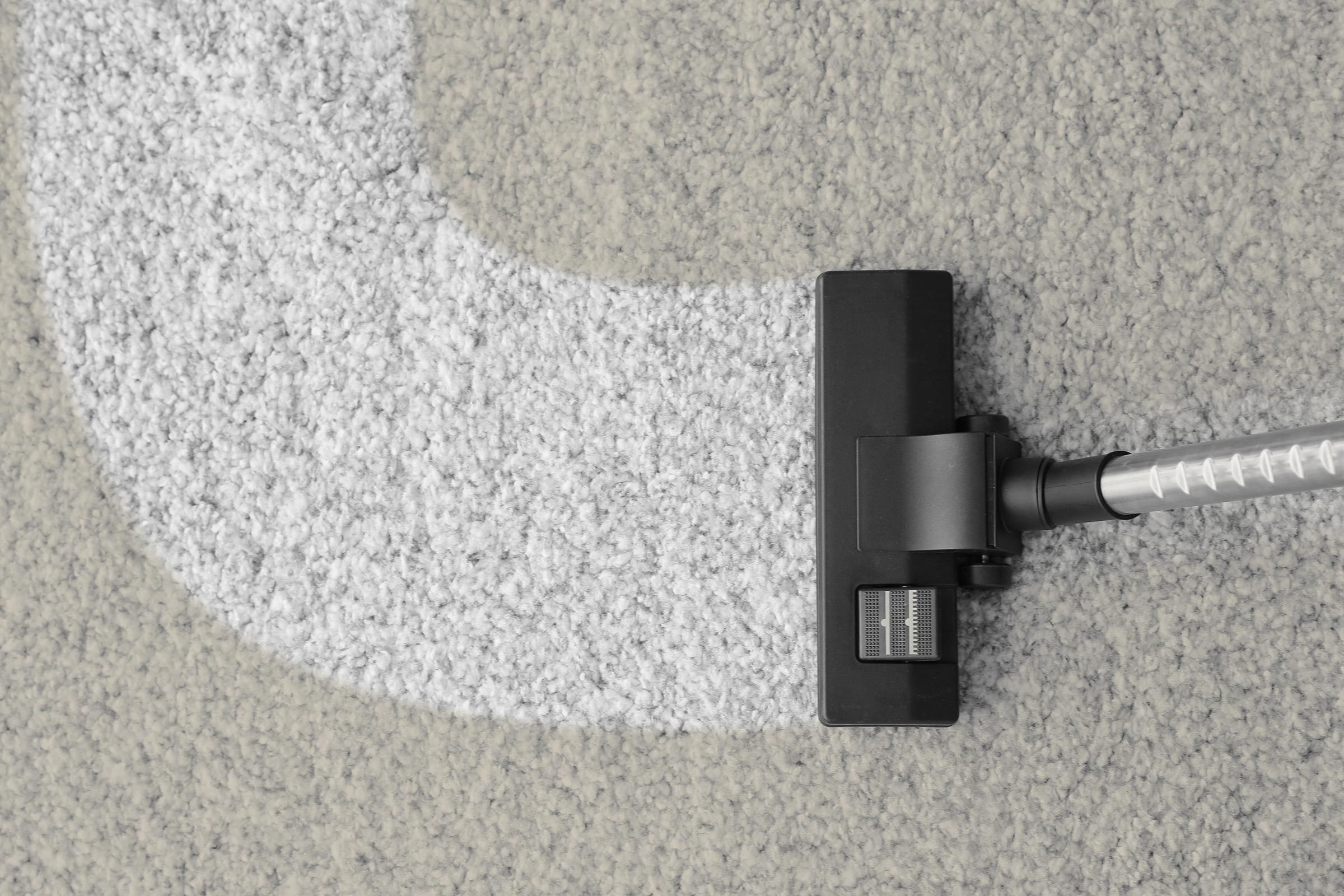 Vacuum cleaner removing dirt from carpet
