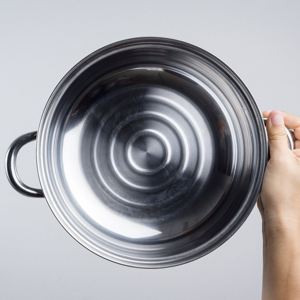 Hand holding stainless steel pan or wide pot on white background