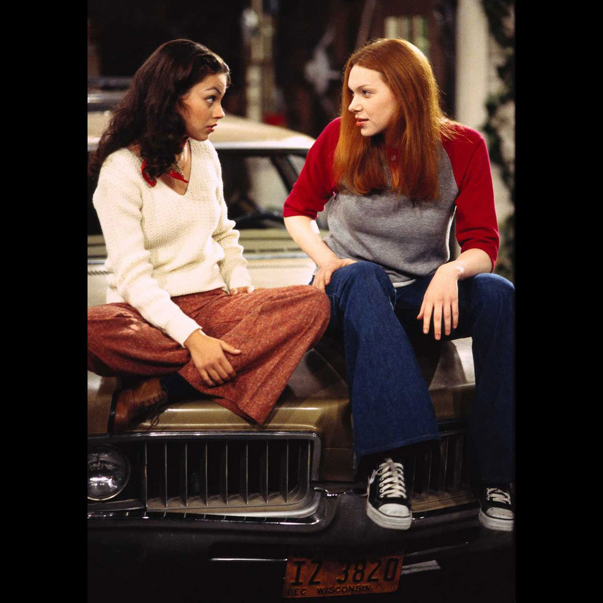 "Mila Kunis and Laura Prepon sit on the hood of a 1969 Oldsmobile Vista Cruiser on the set of ""That '70s Show"""