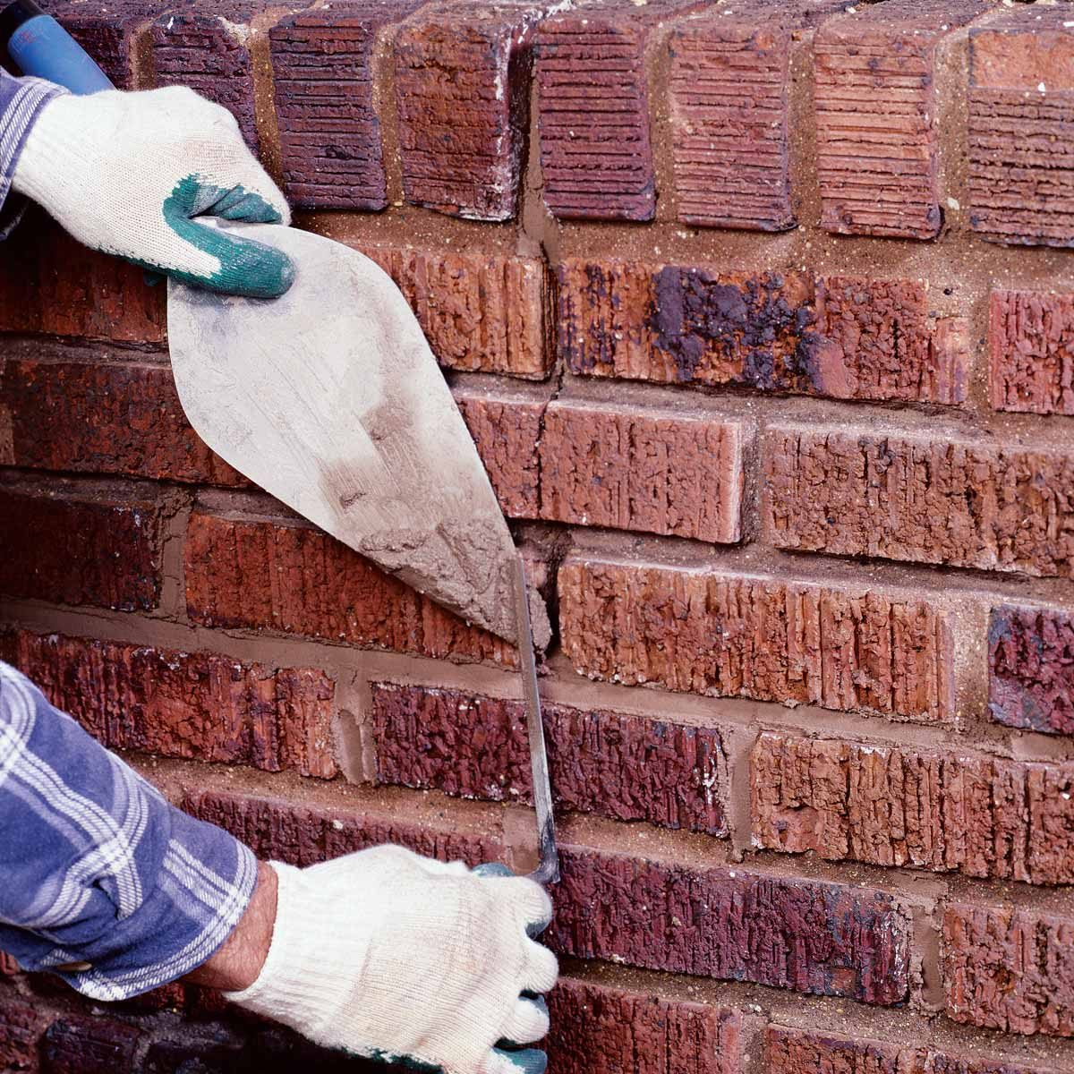 Woman adds motar mix to crack in bricks