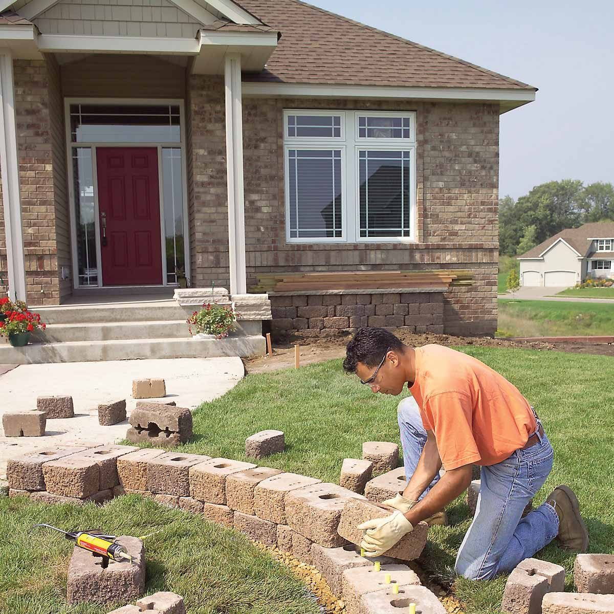 kneeling man adds landscaping stone to front yard