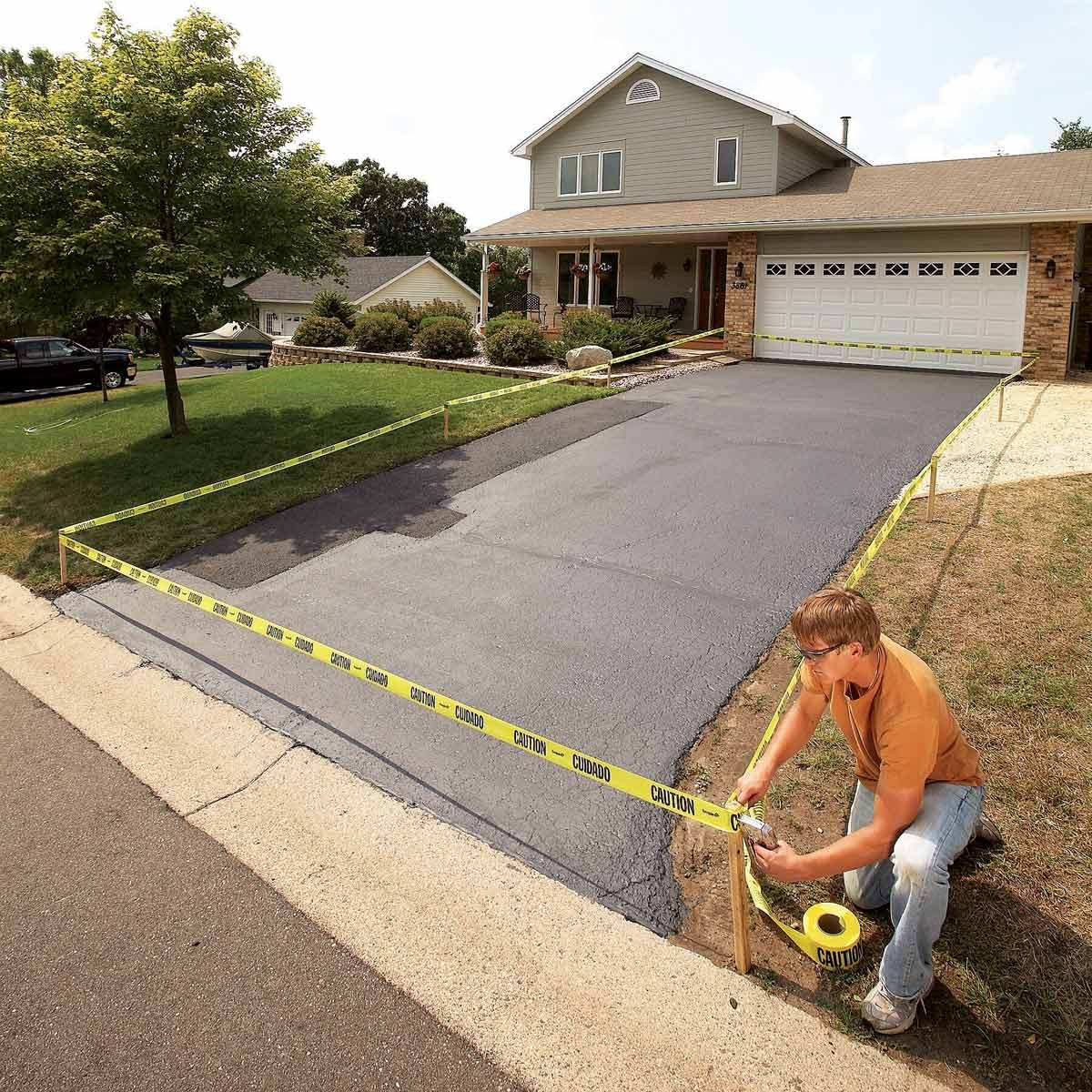 Man-kneels-to-staple-caution-tape-to-post-after-repaving-driveway