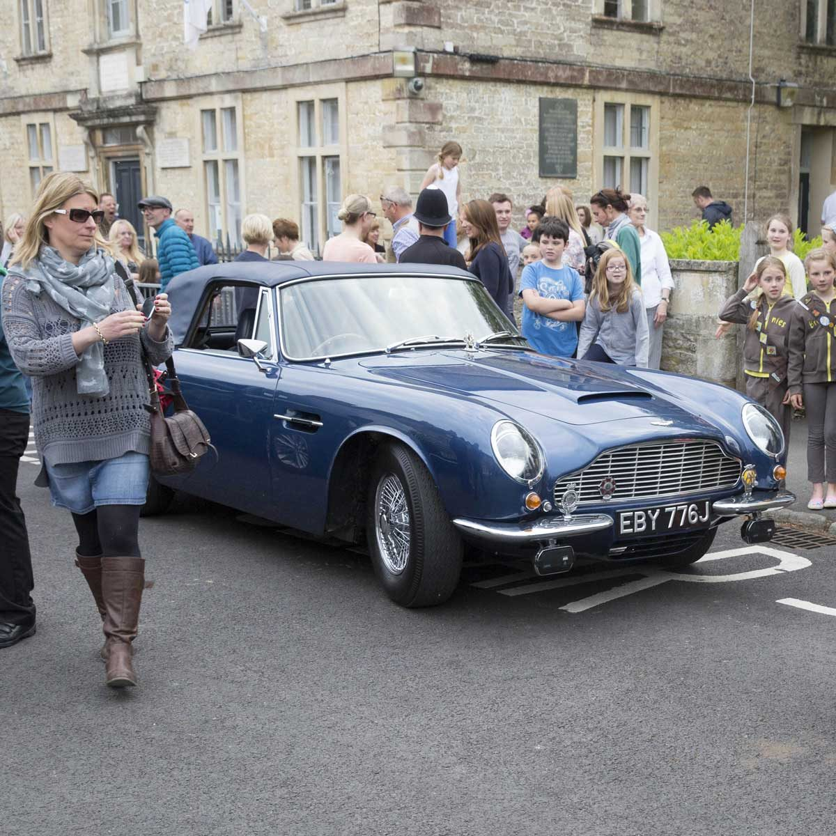 Prince Charles ' Aston Martin acts as a background for people to have their pictures taken standing next to it whilst the Prince was in the concert.