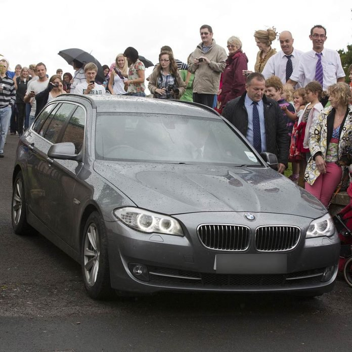 Prince William and Catherine Duchess of Cambridge drive in a gray BMW wagon