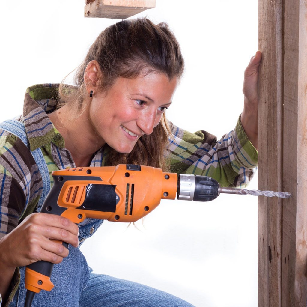 millennial drilling a hole into a door frame