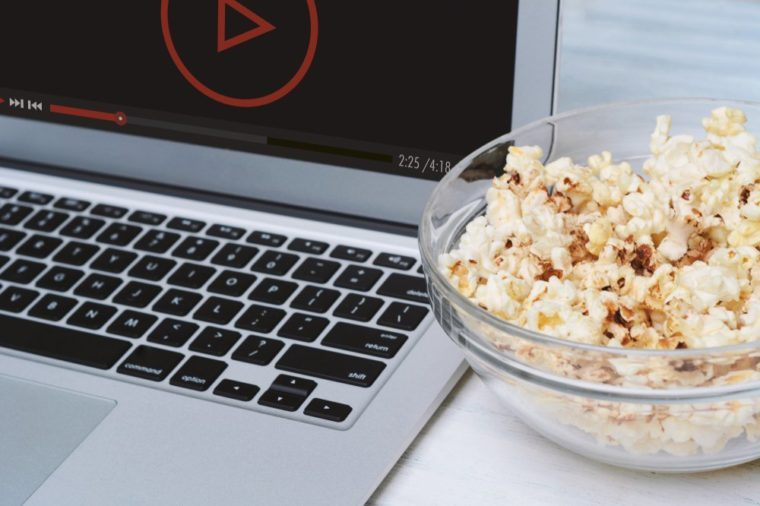Popcorn in bowl and laptop playing movie. Entertainment concept
