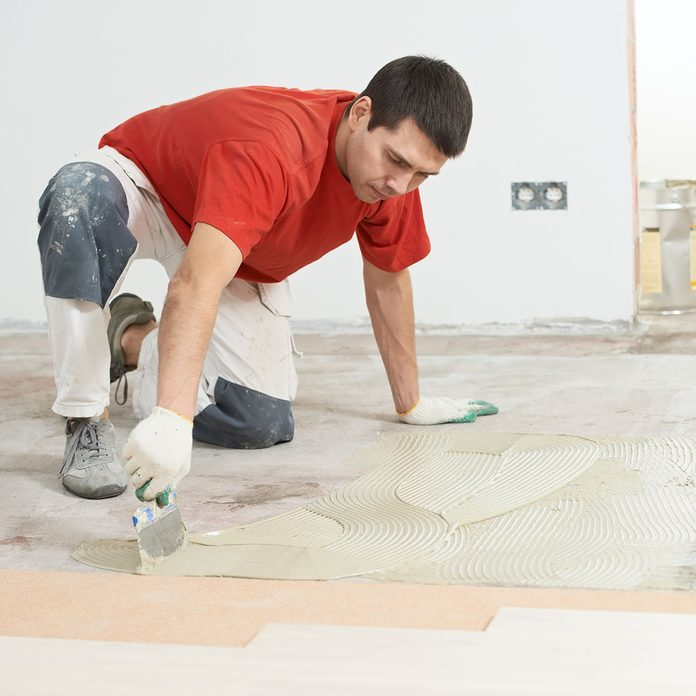 man smearing flooring material on the floor