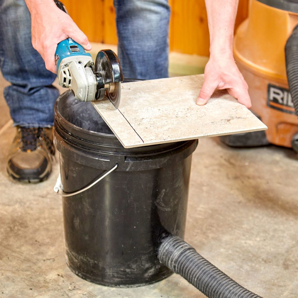 cutting tile on a bucket connected to a vacuum