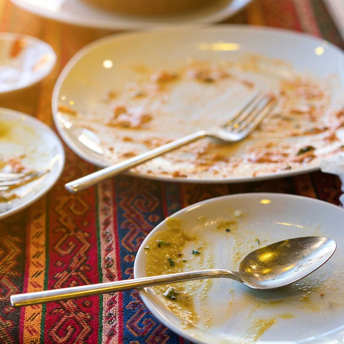 Empty dirty plates with spoon and forks on the table with a bright tablecloth