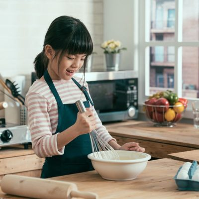 unrecognized mom hands beside in wooden kitchen at home kneading dough on plate. cute happy daughter kid holding whisk mixing flour and eggs for baking bread. child making surprised for mothers day.; Shutterstock ID 1386164354; Job (TFH, TOH, RD, BNB, CWM, CM): TOH