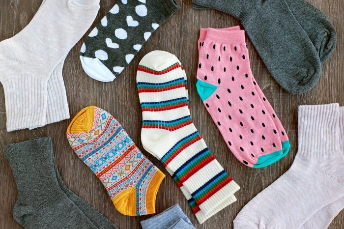 Socks of fine jersey. View from above. Many socks on a wooden background. Socks of different colors and patterns. Clothes for the cold seasons. Knitted clothing. Socks with ornament.