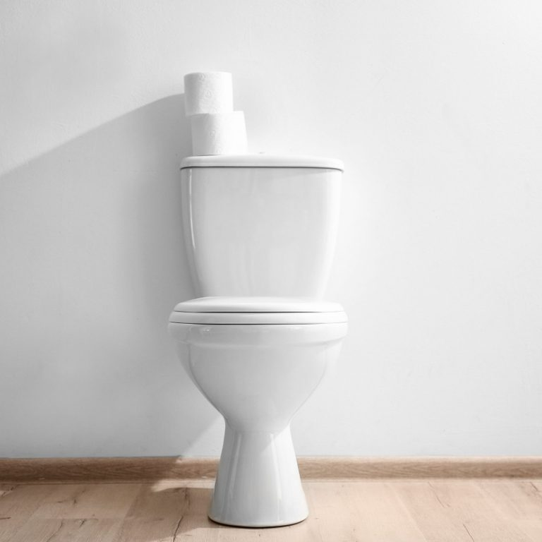 New ceramic toilet bowl near light wall