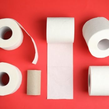 Flat lay composition with toilet paper rolls on color background