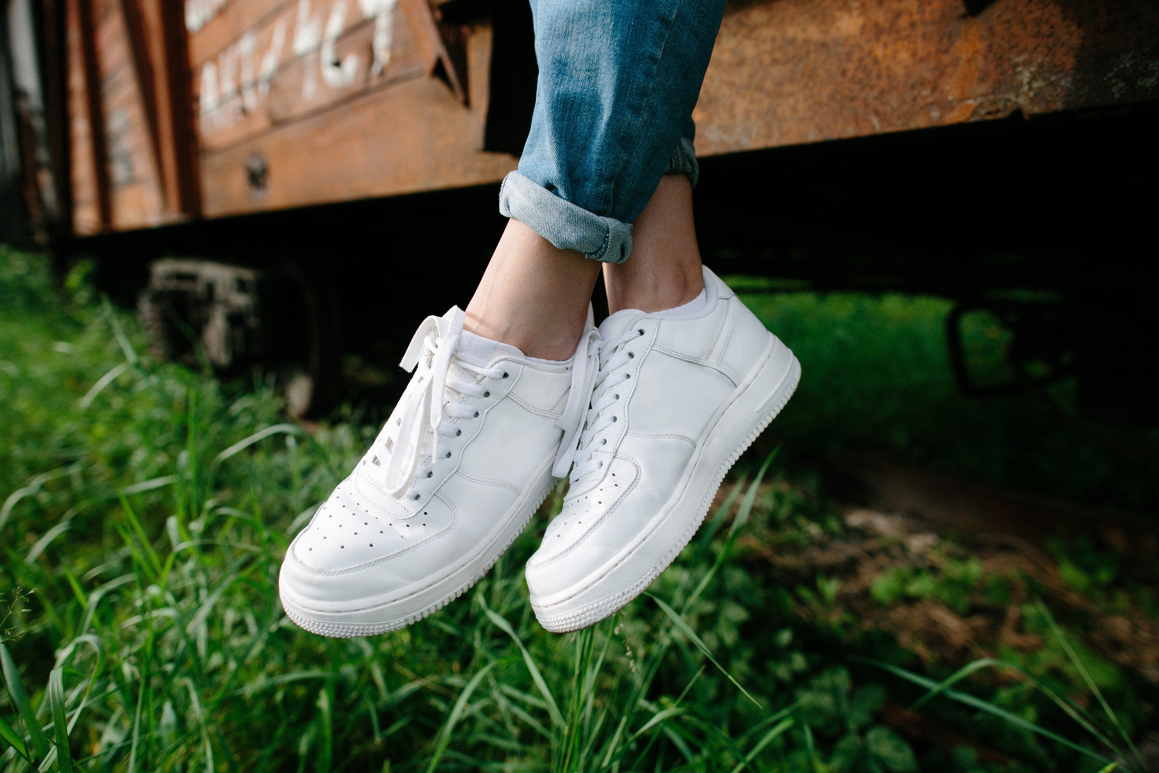 Female sneakers. White female shoes on feet. Sneakers closeup.