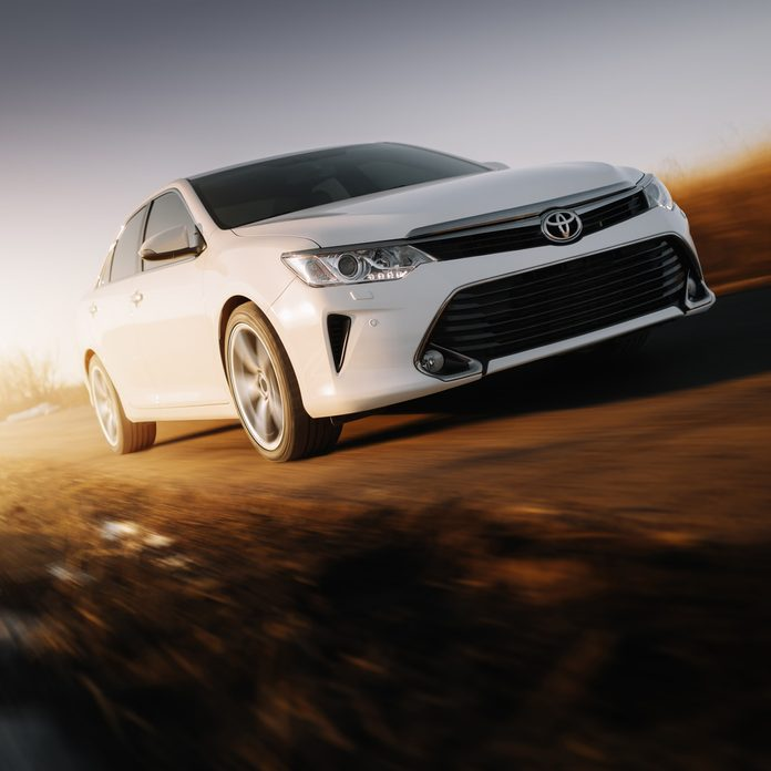 2017: White car Toyota Camry XV50 is driven at empty countryside asphalt road at sunset