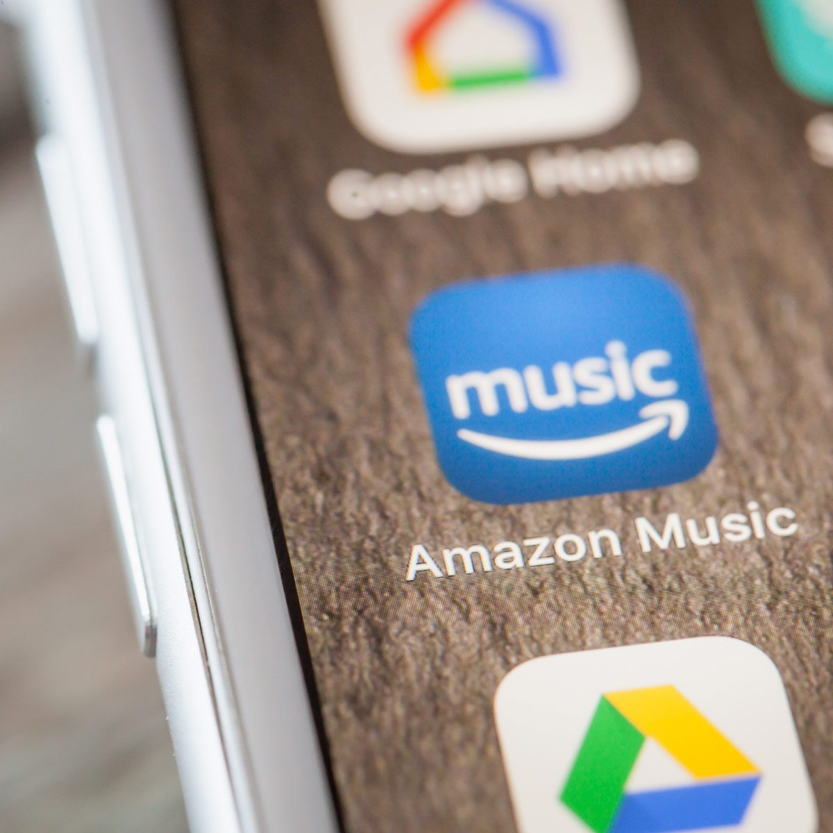 Close-up-to-Amazon-Music-app-on-the-screen-of-an-iPhone-7-Plus-with-personalized-background