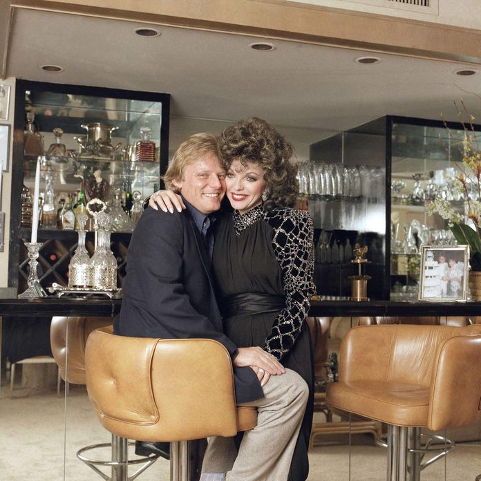 Actress Joan Collins and her husband Peter Holm pose for a photographer in the living room of their home in Beverly Hills 1986