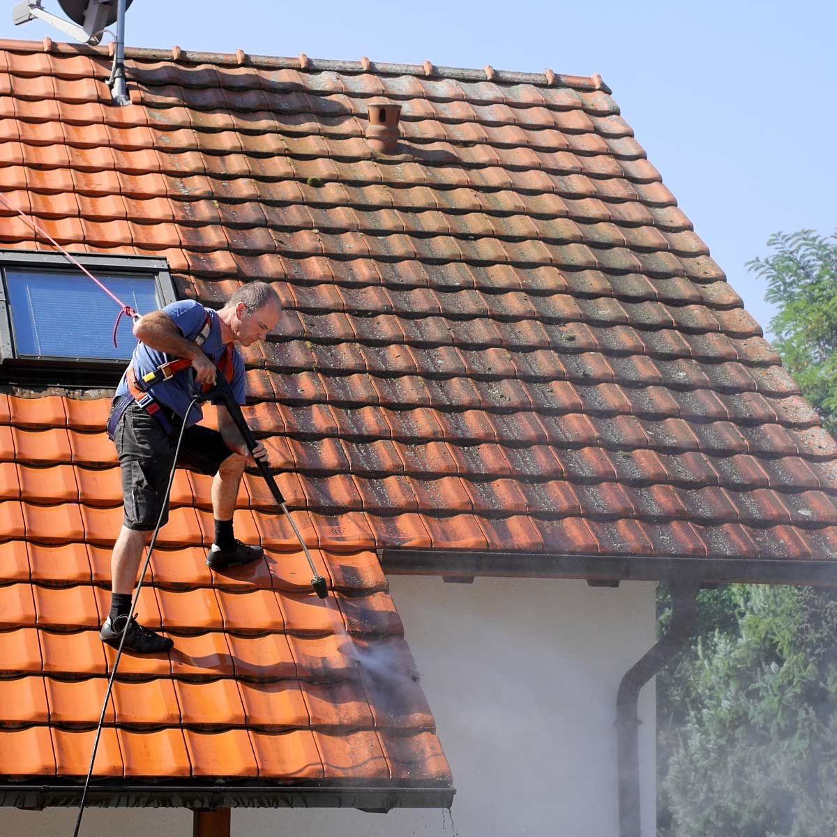 Man-pressure-washes-roof