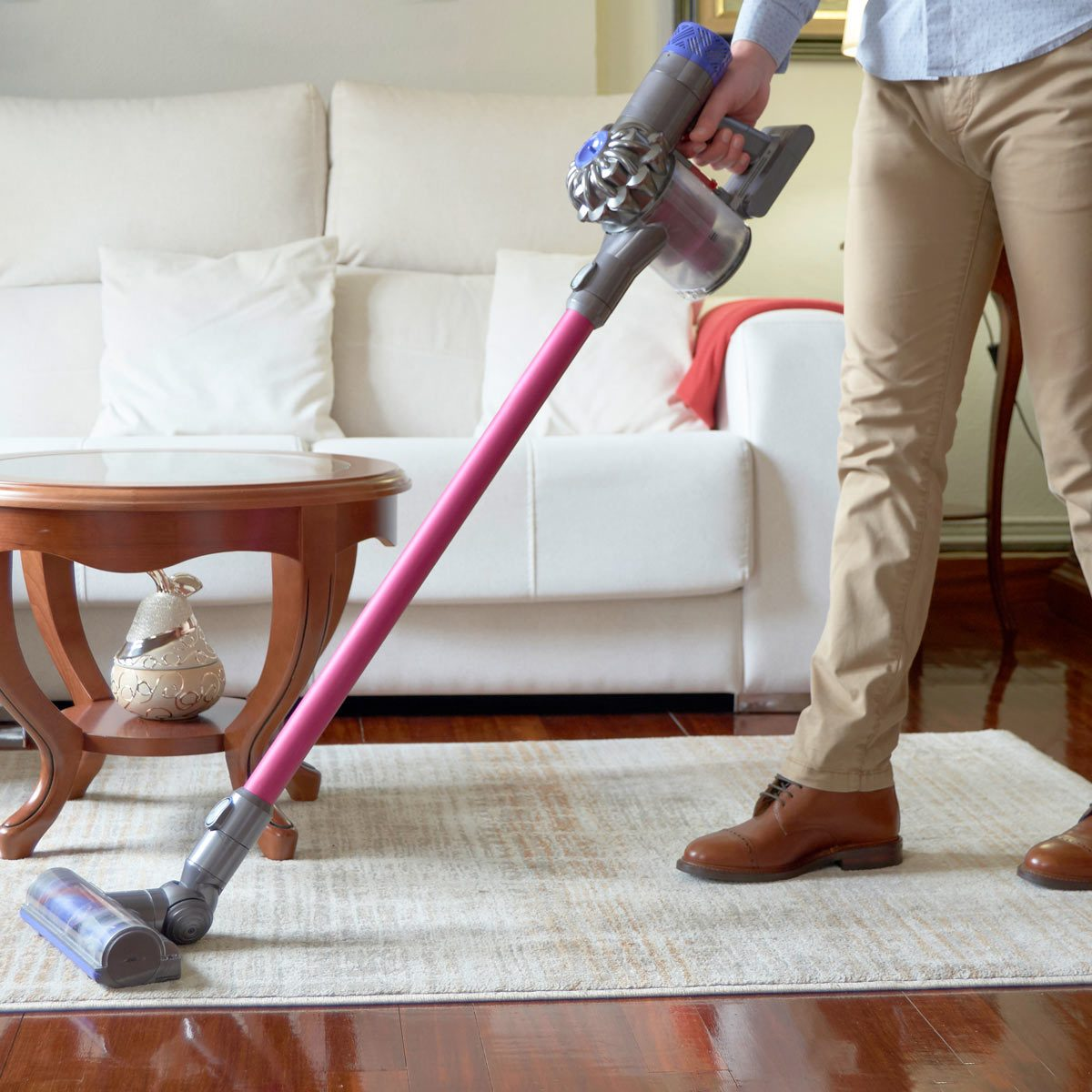 Man-running-a-cordless-vacuum-cleaner-across-the-living-room-carpet