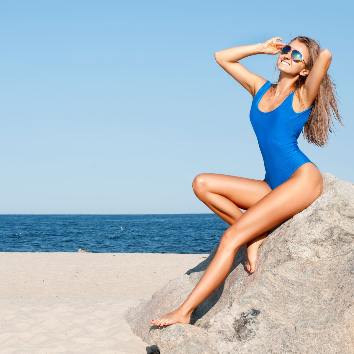 Model-posing-in-a-blue-swimsuit-on-a-rock-by-the-sea