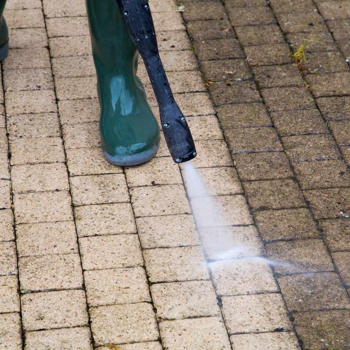Person-pressure-washes-brick