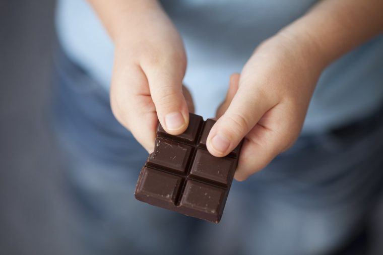 Broken piece of dark chocolate in child's hands.