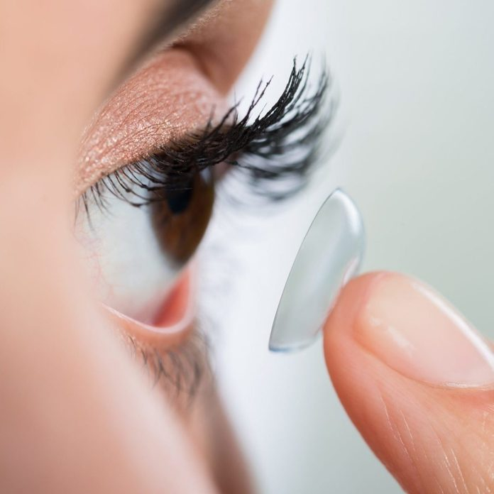 Closeup of young woman wearing contact lens at home