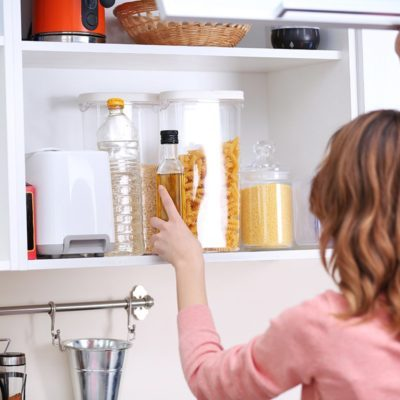 Young woman taking clean dishware in kitchen; Shutterstock ID 410654914; Job (TFH, TOH, RD, BNB, CWM, CM): Taste of Home