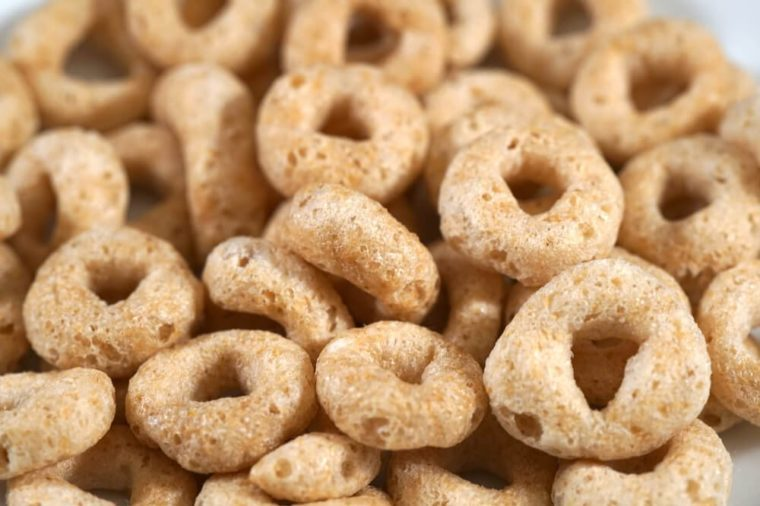 Macro close up toasted oats grain breakfast cereal. Multiple cicle shaped Os in white bowl