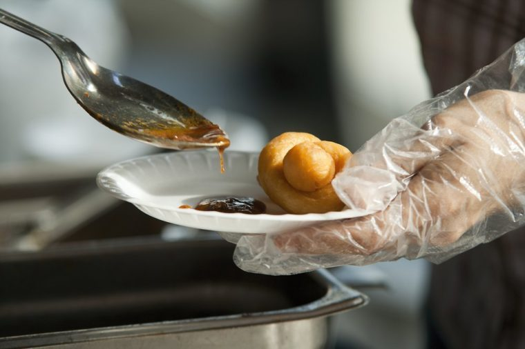 Catering dish up food, Chinese dumplings with sauce. Paper dish with dumpling in one hand and spoon with sauce in another hand.