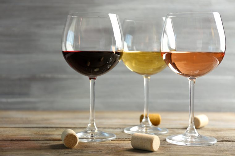 Wine glasses in a row and corks on wooden table against grey background