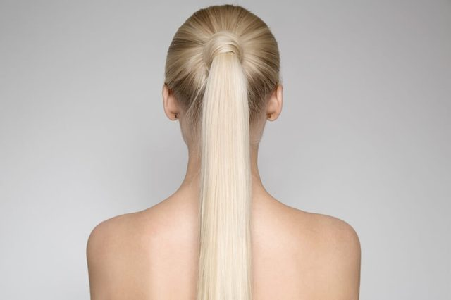 Portrait Of A Beautiful Young Blond Woman With Ponytail Hairsty?le. Back view